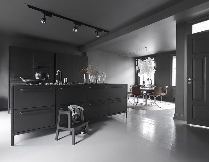 """""""The kitchen is the room we use the most,"""" Sofie says. The dark gray walls and tonal accents make it cozy and cave-like, while natural illumination and light-toned accessories introduce airiness and circulation. Even in the colder months, the Egelunds spend most of their time there, and Sofie maintains that the stark darkness makes it a homey place to entertain guests and spend time with the family. """"And,"""" she adds, """"you can always go to the other floors if it gets too dark!"""" The kitchen…"""
