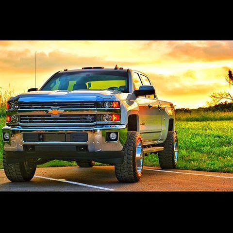 Lifted Silverado Duramax diesel sunset, farm field