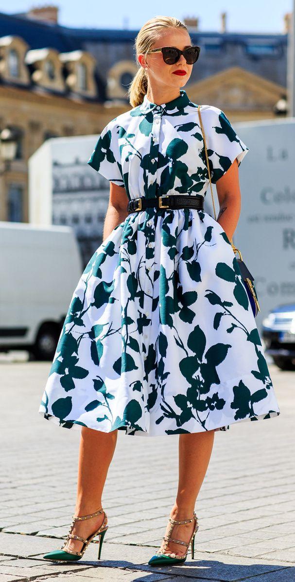Une robe bouffante évasée blanche avec des fleurs vertes foncées avec la taille marquée par une ceinture en cuir, des escarpins en vert et strass et un rouge à lèvres rouge vif.