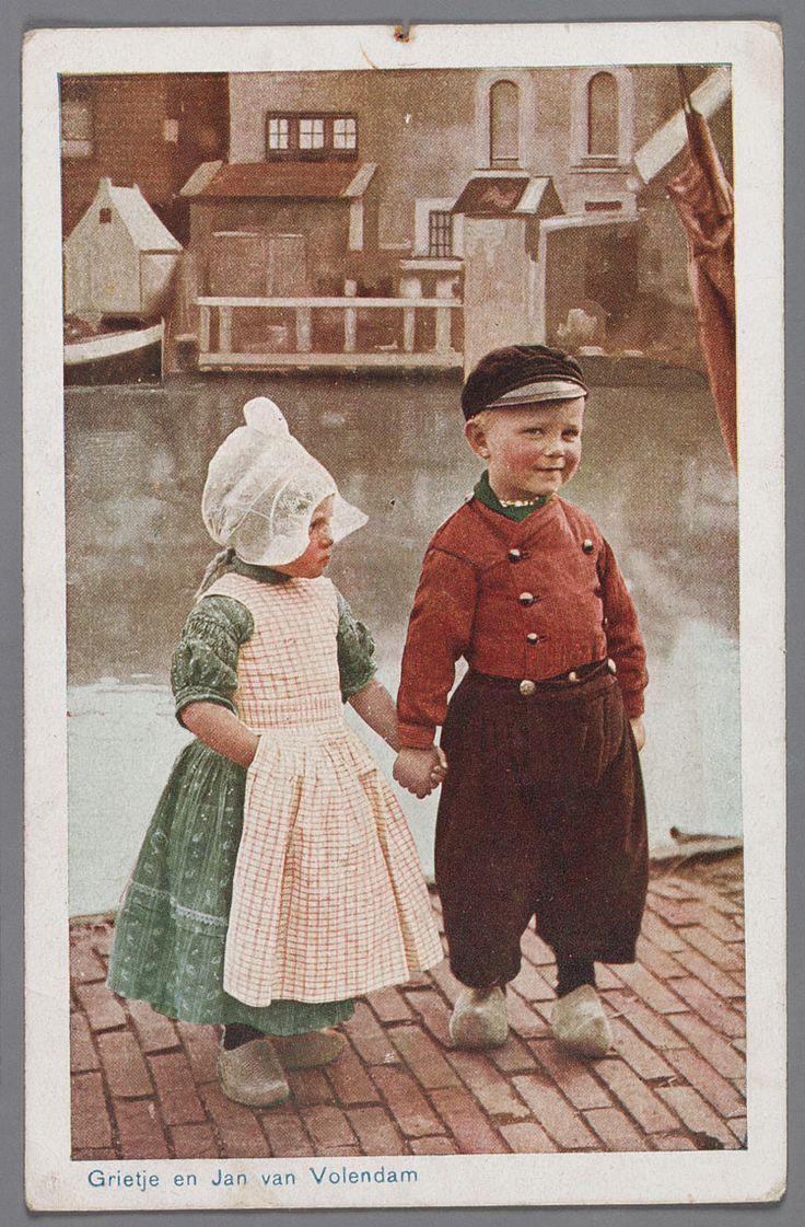 Grietje en Jan van Volendam, 1940-1946 Twee kinderen poseren in dracht. Op de achtergrond het Braakje en het Doolhof, waar een aantal kippenhokken staan. Het meisje draagt een jurkje met daarover het 'lijfbontje' (soort schortje). Deze combinatie word gedragen tot het vierde levensjaar. #NoordHolland #Volendam