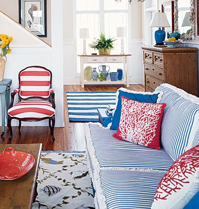red striped chair, ticking stripe on couch, coral pillows - very nautical vibe