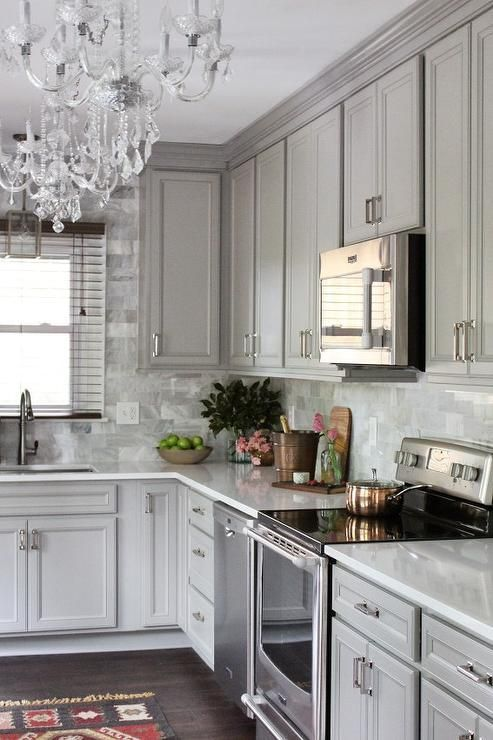 Gray kitchen features gray raised panel cabinets paired with Viatera Snow  Storm