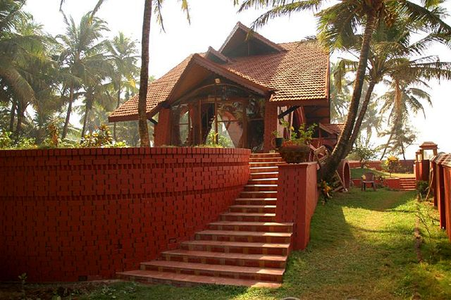 Korlai Bungalow: Exterior view of bungalow taken from the wall of the compound (the sea is located at right). The vault of one bedroom is visible at center right. Steps lead up from the garden to the main living area   Archnet