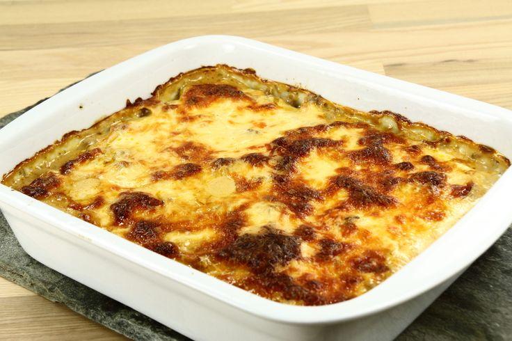 Skræl kartoflerne, skær dem i skiver og tør dem. Varm olien og rist kartoflerne heri ca. 10 min. Læg de halvstegte kartofler i bunden af et oliesmurt ovnfast fad. <BR> <BR> Pil og hak løgen