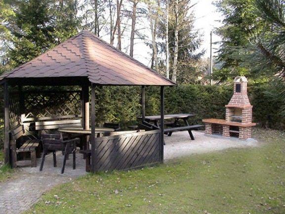 Zahradní krb Beskyd se stolkem s fasádou Marmolit 214,úprava cihla malá. Krb má udírničku v komíně a zarovnané a vyšamotované boky topeniště.