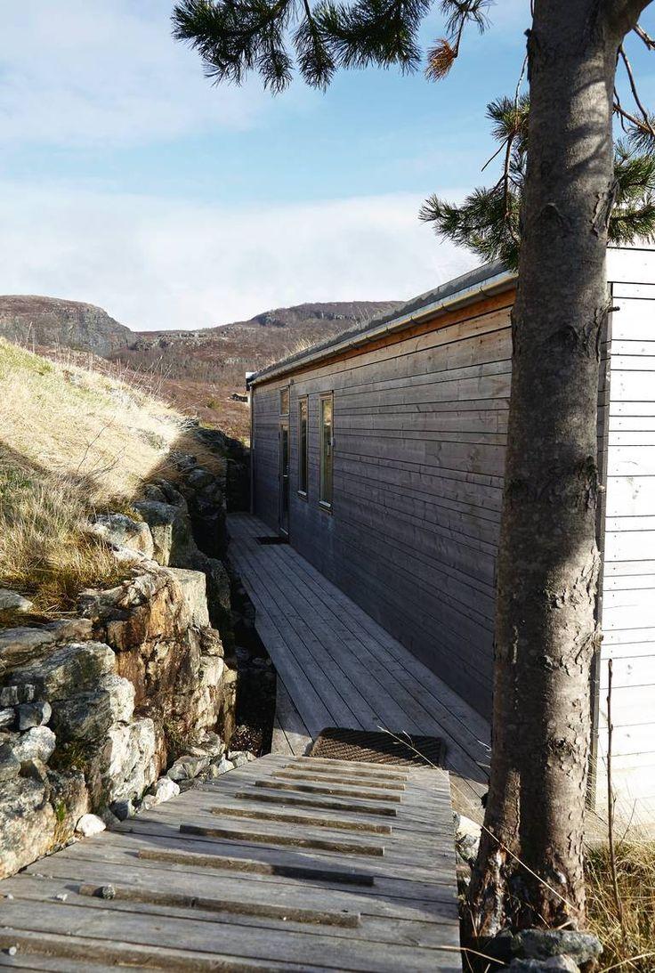 INNGANG I LE: Mye værkommer på kort varsel her ved denne hytta på Stokkøya ved kysten av Trøndelag. Ankomsten og inngangsdøren er kloktnok trukket inn mot bergveggen.Eksteriøret i kjernefuruhar grånet med årene.