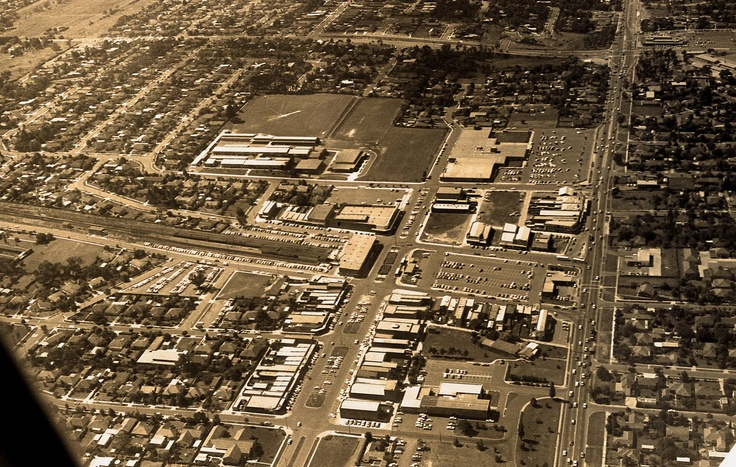 "An aerial view of Glen Waverley, 1972. Springvale Road runs from top to bottom at the right of the picture, and High Street Road runs from left to right near the top. The small original ""The Glen"" shopping centre has since been extended all the way to High Street Road with some streets and many houses having disappeared."