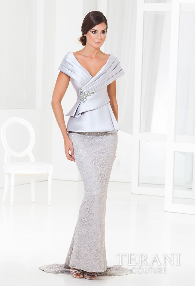 Evening gown with satin peplum top and crystal detail at the waist with pleated shawl collar. It is finished with a mettalic lace skirt and sweeping train