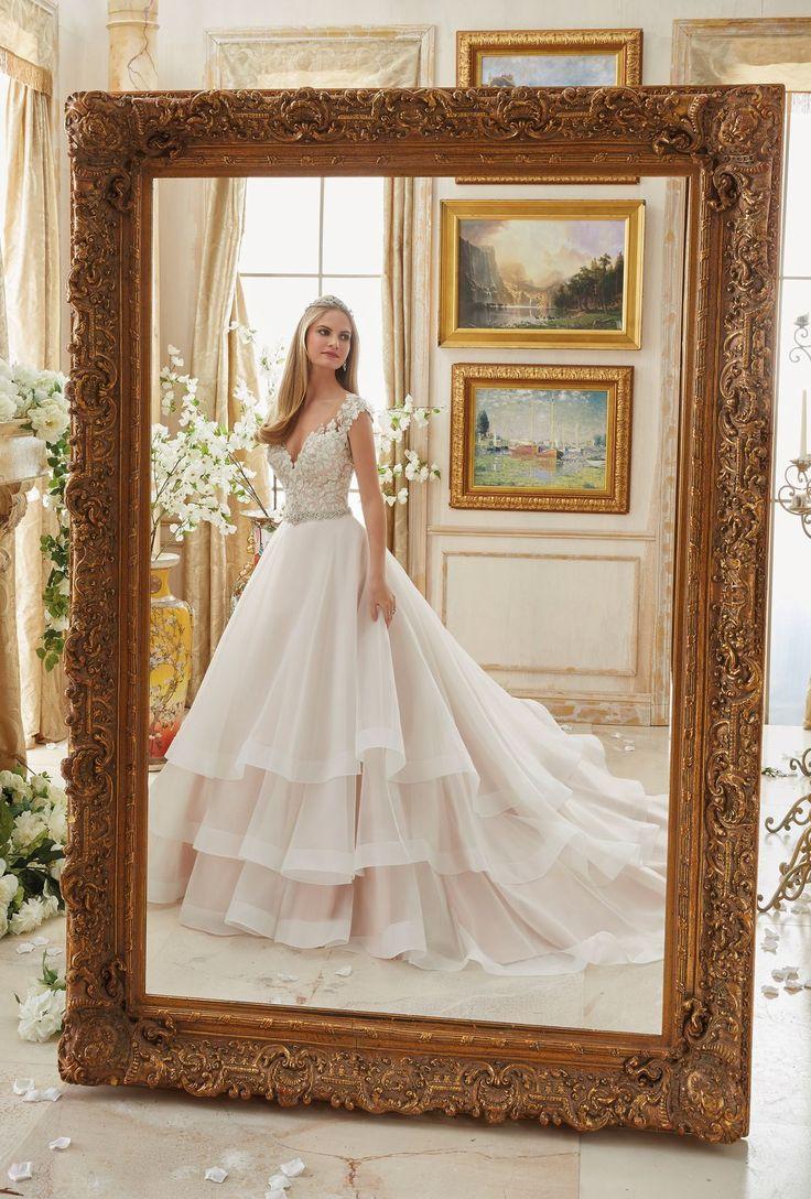 Niepowtarzalna suknia ślubna Mori Lee z haftowanym gorsetem i wielowarstwową spódnicą z organzy. Projektantka Madeline Gardner zaprojektowała tą suknię byś …