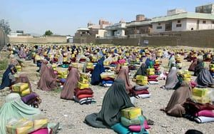 Burqa-clad women receive aid distributed by the Ummah Islamic charity in Kandahar, Afghanistan