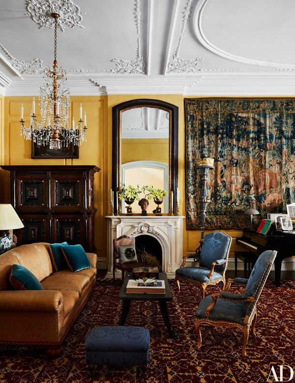 An antique tapestry hangs in the grand living room, where a Couturier-designed sofa is dressed in a Christopher Hyland fabric; the armchairs and stool wear Stark textiles. Walls painted in Farrow & Ball's Sudbury Yellow.