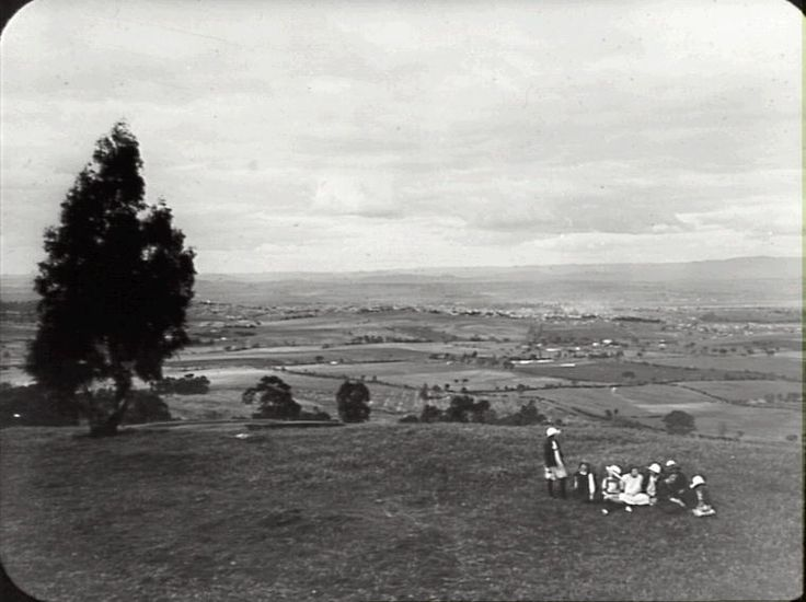 Title: Bathurst from Bald Hill, N.S.W Date: Not given Location: 	 Bald Hills (NSW); Bathurst (NSW) Description: Black and white glass lantern slide. Title from cursive ink inscription on lower edge. Notes: Group of girls on top of grassy hill with solitary tree, looking down over agricultural land to the town of Bathurst.