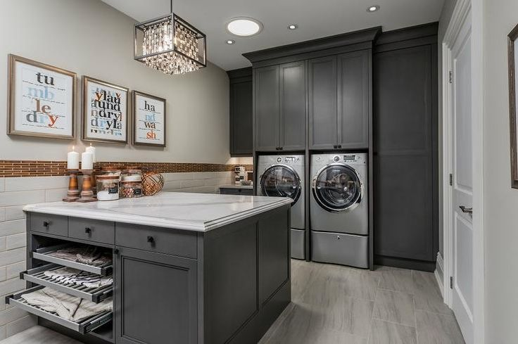 Charming gray laundry room boasts a gray front loading washer and dryer enclosed beneath and between dark gray cabinets accented with matte black hardware.