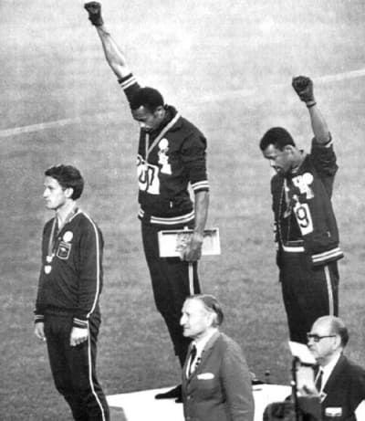 El Saludo del Poder Negro en los Juegos Olímpicos de 1968: Los atletas afroamericanos Tommie Smith y John Carlos levantan sus puños como gesto de solidaridad en los Juegos Olímpicos de 1968. El medallista de plata australiano, Peter Norman, llevaba una insignia del proyecto Olímpico por los Derechos Humanos en apoyo a su protesta. Como resultado, ambos estadounidenses fueron expulsados de los juegos.