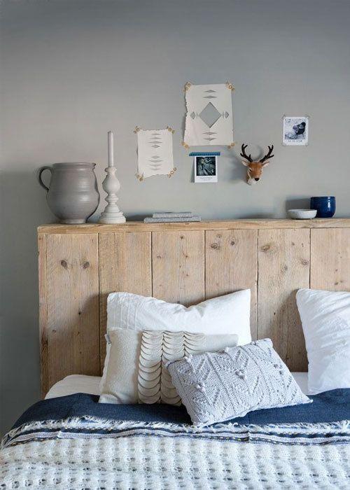houten hoofdeind | decoratie: posters, vaasjes, kaarsenstandaard, hertenhoofd | blauw dekbed