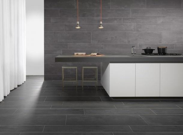 Keuken met grote tegels op vloer en wand.