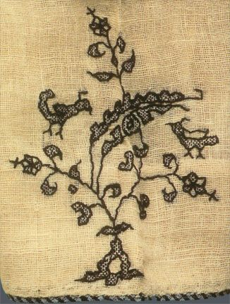 Close up of motif on 14th c. Eastern Persian pirihan/under tunic. Each segment is decorated with a sequence of motifs comprising a flowering tree with a root out of which grow leafy branches, flanked on either side by a long-tailed bird perched on a branch with its wings outstretched. Height 130 cm (51 ins.), width 219 cm (86-1/4 ins.). Cotton, balanced plain weave, gauzy. Decoration : silk, chain stitch and running stitch embroidery, brocading.
