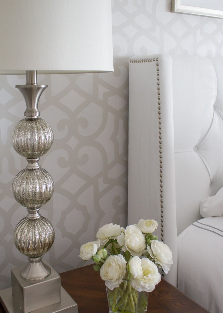 stenciled wall behind white upholstered headboard