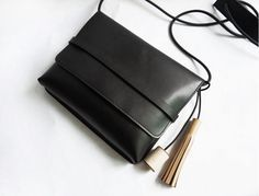 Simple Black Leather Crossbody bag with wood and leather tassel by CloudAndRock on Etsy https://www.etsy.com/listing/231490117/simple-black-leather-crossbody-bag-with