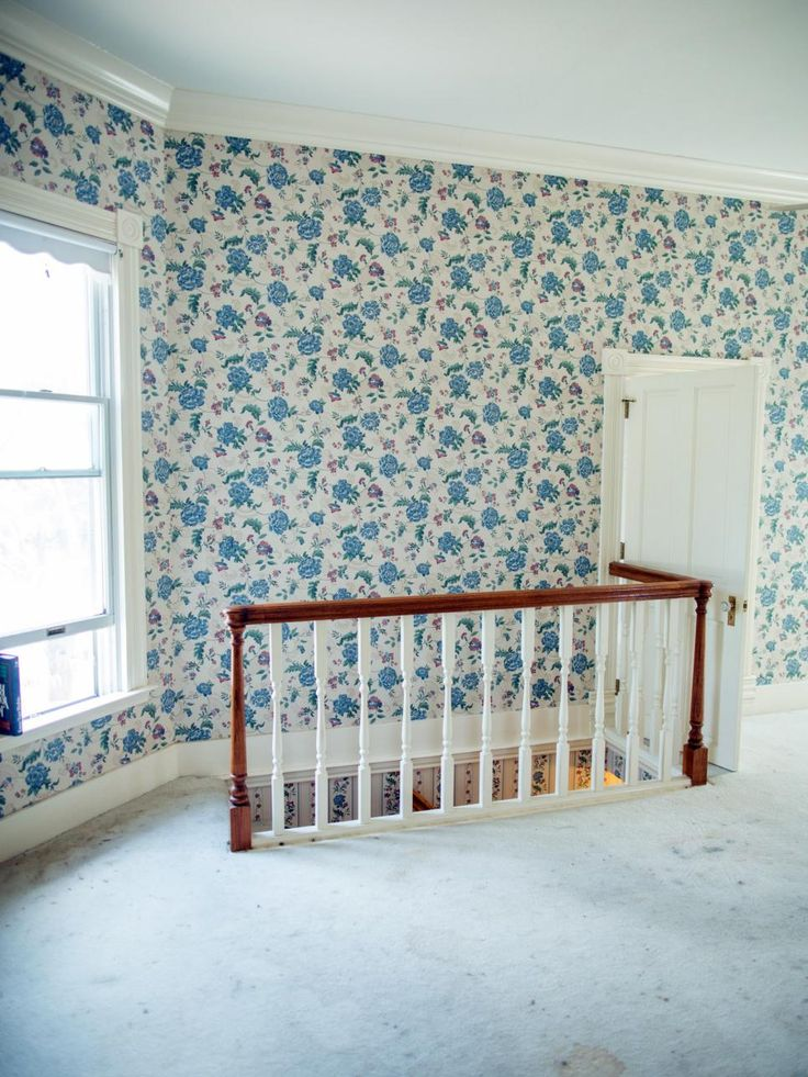At the top of the stairs is a spacious landing with lots of light but worn carpeting and dated railing and wallpaper.