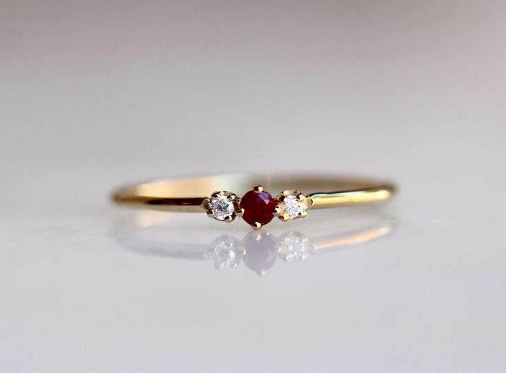 This ring is so sweet. This ring gives and hint of red and a hint of sparkle with its lovely tiny stones.Center Ruby - 2 mm Side diamonds- 1.3 mmRound band measures 1mm in thicknessHa...