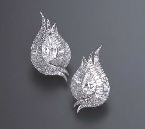 A PAIR OF DIAMOND EAR PENDANTS, BY JULIUS COHEN Each designed as a tapered baguette-cut diamond scroll, centering upon a pear-shaped diamond, weighing approximately 2.76 and 3.01 carats, mounted in white plated yellow gold Signed Julius Cohen