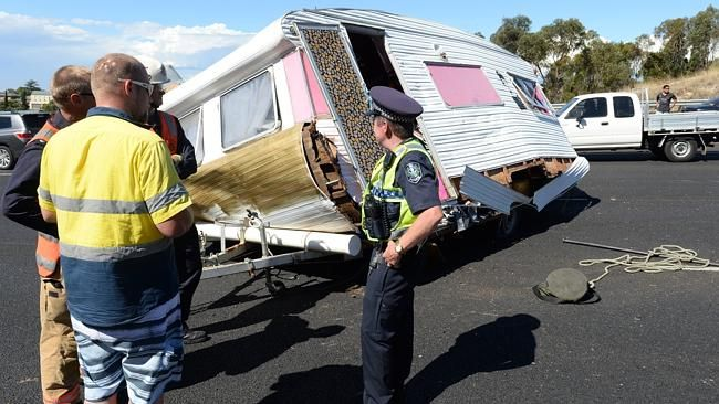A car towing a caravan has flipped on the downtrack of Southern Expressway