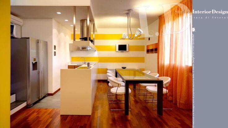 Cucina e zona pranzo con bancone corian e cappa ad isola inox www.studiointeriordesign.it