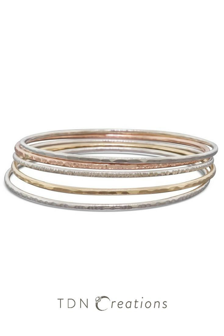 This set of 5 gold and silver stacking textured and hammered bangles would add that extra sparkle to any outfit!    - 3 sterling silver bangles: faceted, textured with small lines and textured with big lines   - 1 yellow gold bangle: faceted   - 1 rose gold bangle: textured with big lines    If you wish to have a different combination, please let me know!  I made these bangles with 1.6mm (14 gauge) solid gold wire and have polished them to a bright shine.