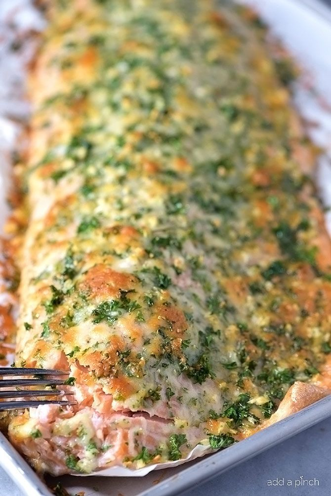 Baked salmon makes a weeknight meal that is easy enough for the busiest of nights while being elegant enough for entertaining. This oven baked salmon with a Parmesan herb crust is out of this world delicious! // addapinch.com