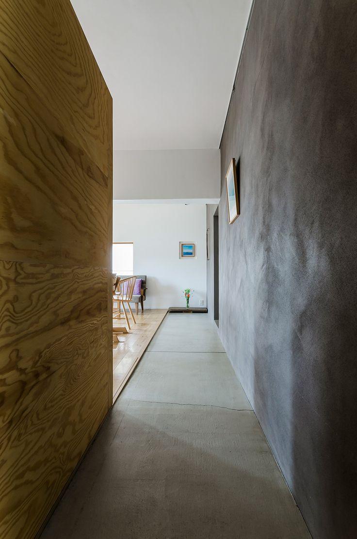 玄関を開けると広がる光景。ラーチ合板の扉は手前の書斎だけでなくキッチンまでをカバー。その先にさしこむ光も、奥行きを感じさせる演出のひとつ。