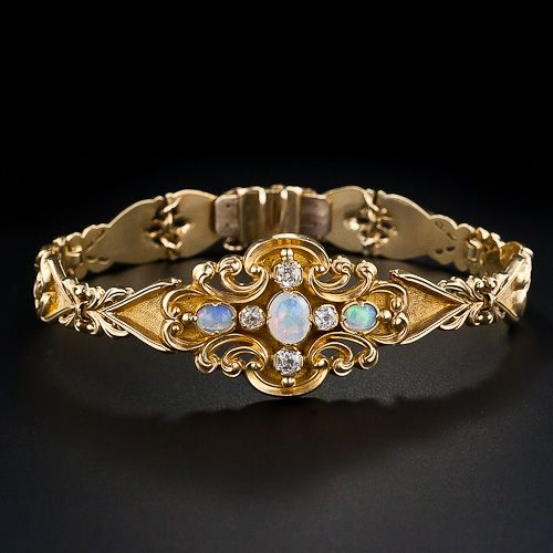 A graceful scroll motif opal and diamond bracelet from the early Victorian period with a prescient Art Nouveau feel. The central plaque feature three glowing white opals and four sparkling old mine-cut diamonds. A truly lovely and graceful antique bracelet, circa 1850. This bracelet has a double box catch with a snake safety chain and measures about 6 3/4 inches long by 3/4 inch wide.