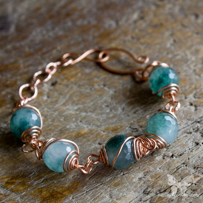 Gorgeous, faceted teal-green agate stones (approx 10mm) wrapped in copper wire swirls.  Very dramatic and beautiful on its own, or with a stack of mixed metal bangles!  Perfect for those who like a less dainty bracelet.  The beads have been wrapped by hand, and the infinity & hook clasp is al...