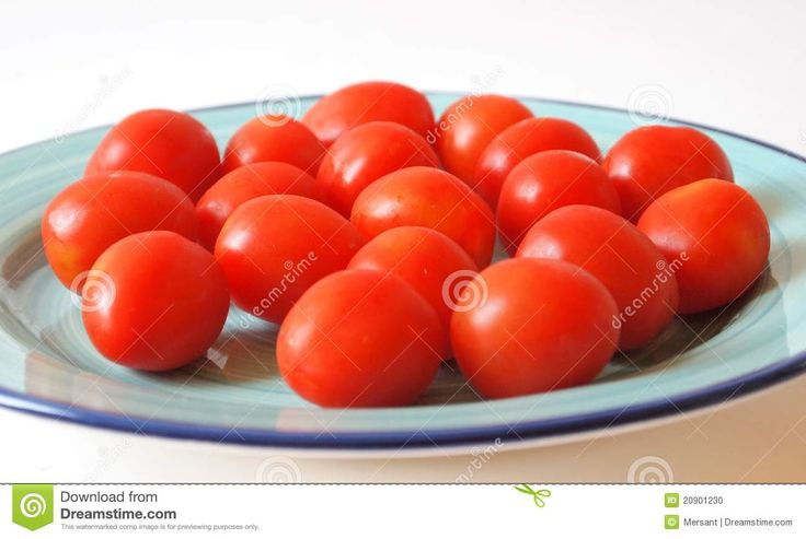 Some cocktail tomatoes on a green plate