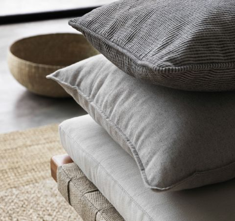 A close-up of cushion covers in white, grey and black/white stripes.