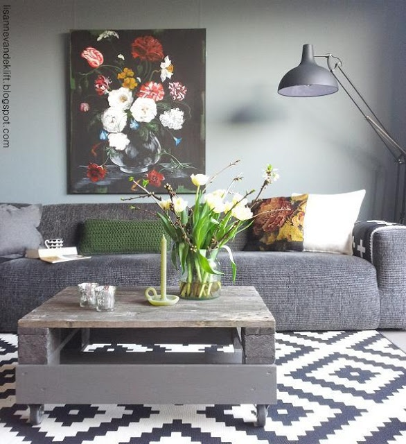 living room full of gray with a floral art piece - black background with white and pink flowers