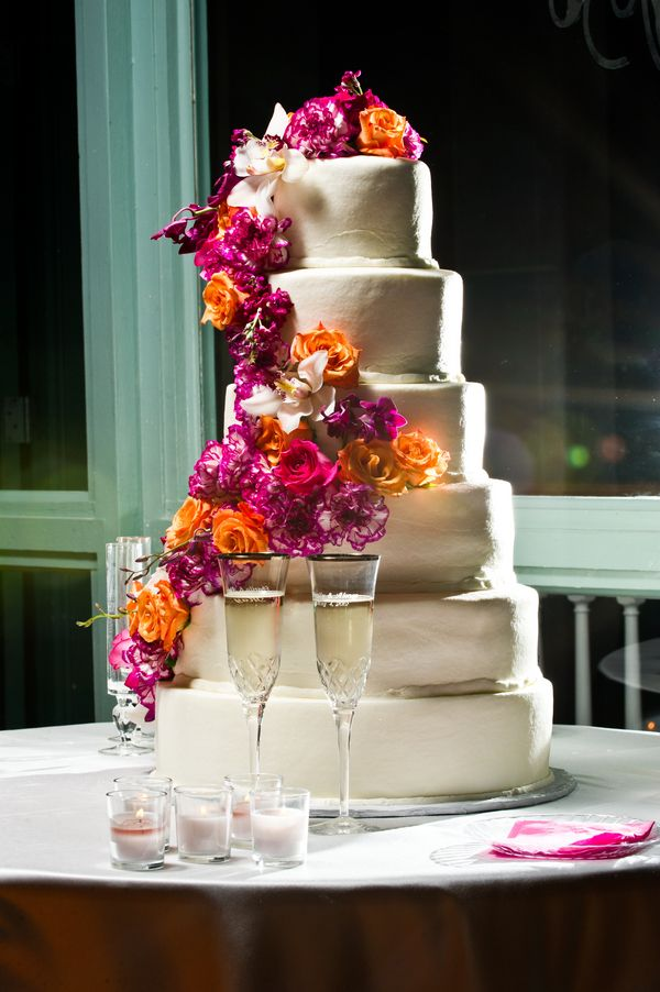 Flowers add pops of color; fuchsia and orange flowers; wedding cake