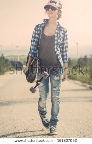 Beautiful Young woman walking and holding a skateboard - stock photo