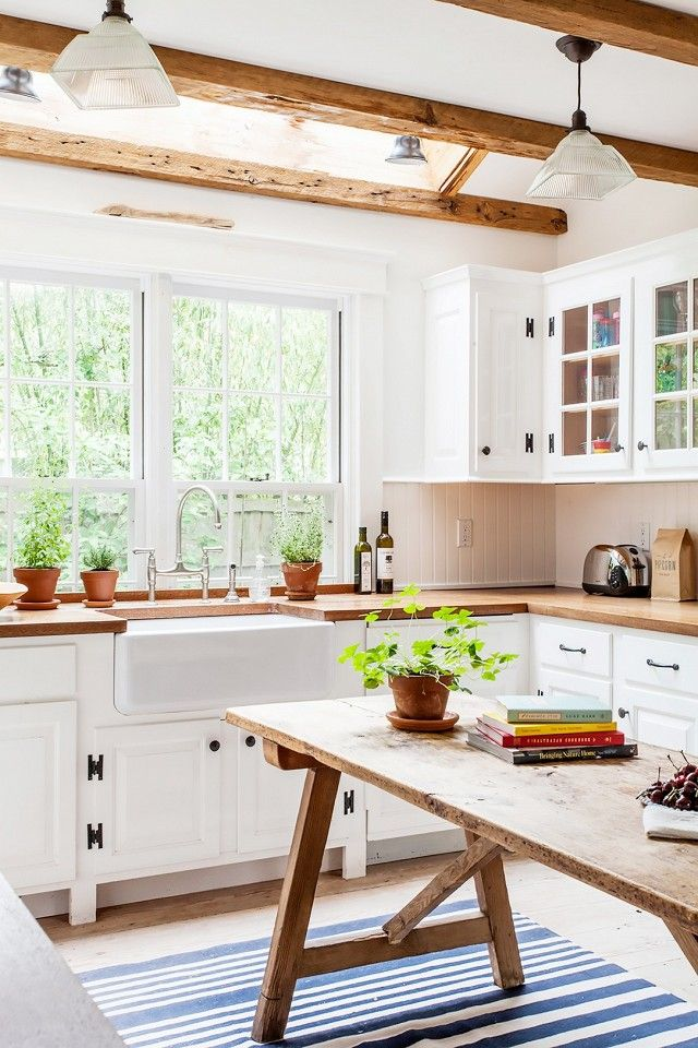 Cottage farmhouse kitchen with vintage beams, blue-and-white stripes, and rustic accents