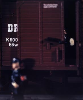 What looks like a train arriving at a concentration camp, the door just opened  and you can just see the people inside.