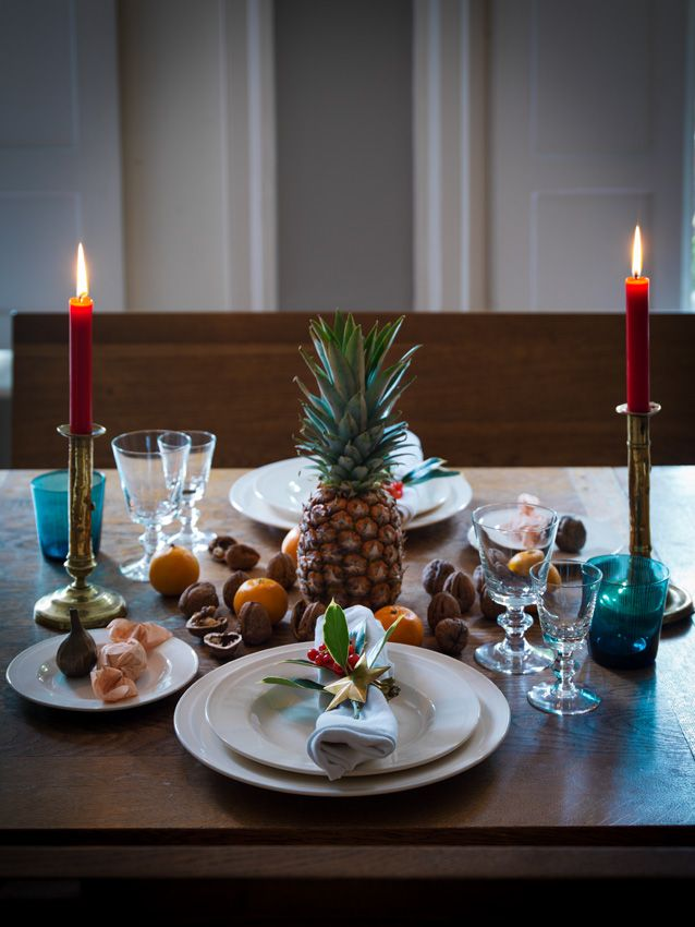 simple and sweet, English Holiday Table, Ben Pentreath, place setting with clementines and nuts as table decor, brass candlesticks with red candles, pineapple in the center