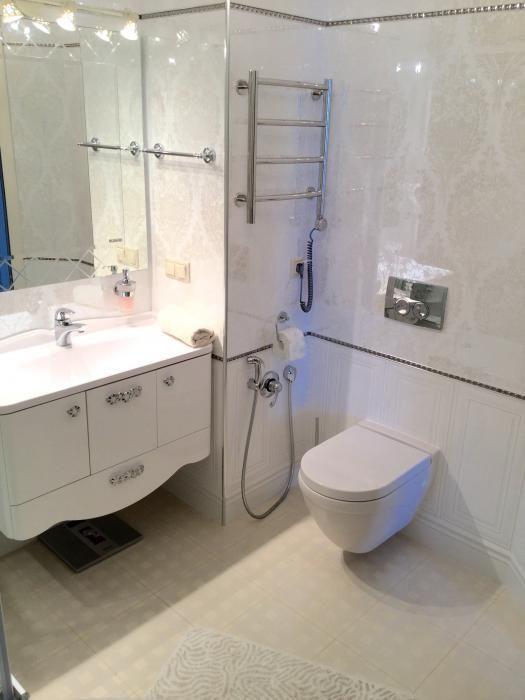 Интерьер белой ванной, подвесной унитаз с гигиеническим душем
