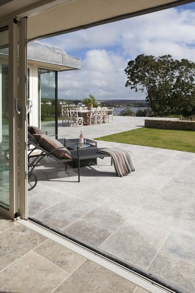 Milan Tumbled limestone from Mandarin Stone - Looking as if it has been walked on for centuries, this worn looking Limestone with rounded corners and edges creates real authenticity. A popular choice for those wanting a warm grey flagstone in large formats.