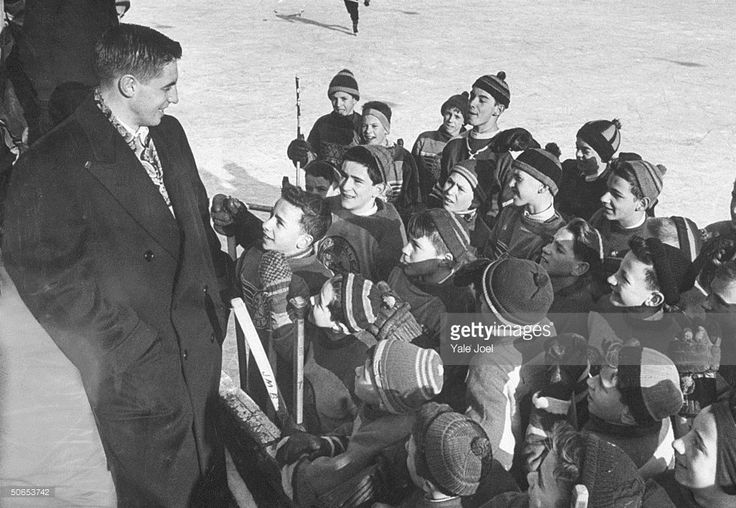Ice Hockey player Jean Believeau, greeting children at an outdoor skating rink causing much attention. Quebec, Canada, 1952