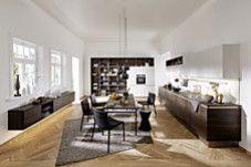 Unter der Bezeichnung ARTWOOD vereint Nolte Küchen attraktive Holzdekore für das knappe Budget, unter anderem in der Variation Nussbaum Kuba – hier gepaart mit mattweißen Fronten bei den Hoch- und Hängeschränken. Offene Regale und ein schwebend montiertes Sideboard öffnen die Küchenlandschaft zum Wohnbereich hin.