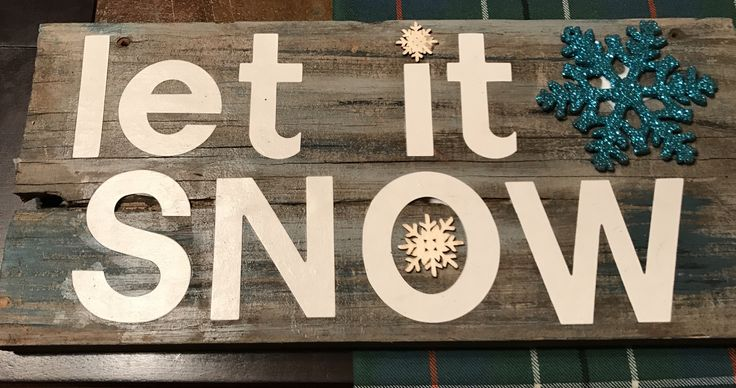 Decoupage words on barn board with snowflake embellishments.