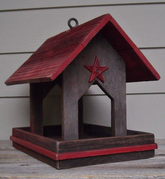 "Etsy. ""This red and brown primitive bird feeder is covered to keep the food dry. It is made of reclaimed cedar fencing and the open plan invites the birds in (and probably the squirrels, too!). It has a red roof, red trim at the base and a red metal star at each end. It can be mounted on a post or hung by the eye screw on the top."""