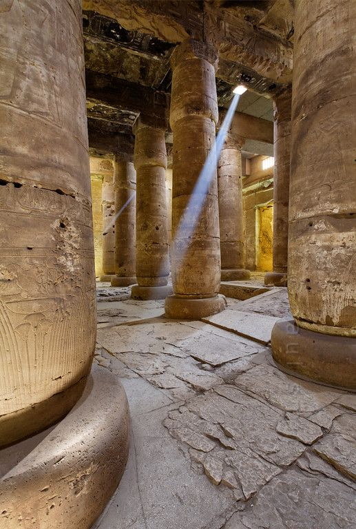 'Second Hypostyle Hall of Seti I Temple at Abydos.'  A sun beam piercing through a a hole in the roof illuminates the Second Hypostyle Hall of the Seti I Temple at Abydos. The hall has several of these holes, which are part of the original design to provide lighting. Behind the columns, to the right, we see the entrance to the Chapel of Ptah. The temple was begun by Seti I and completed by his son Ramses II in the 13th century BC. Photo Paul Smit.