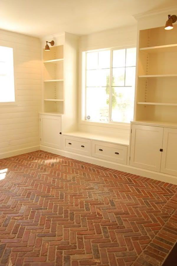 Horizontal planked walls, built-in storage with library-style lights & window seat, worn brick flooring in herringbone pattern