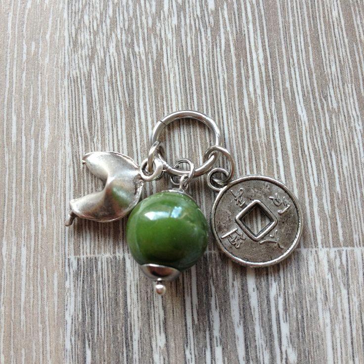 Bedel van 12mm groen keramiek kraal, metalen Chinees geluksmuntje en een forten cookie. Van JuudsBoetiek; €2,50. Bestellen kan via juudsboetiek@gmail.com, via persoonlijk bericht of www.juudsboetiek.nl.